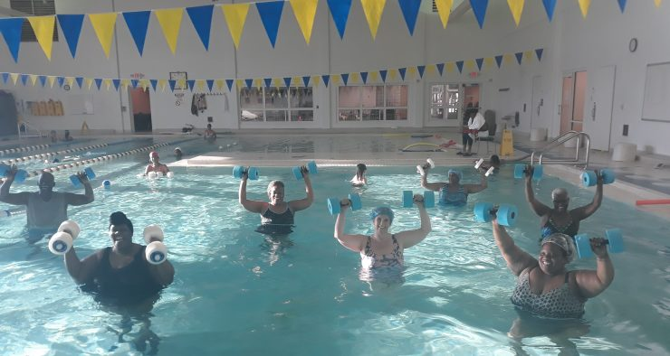 a group of older people is exercising in an indoor pool