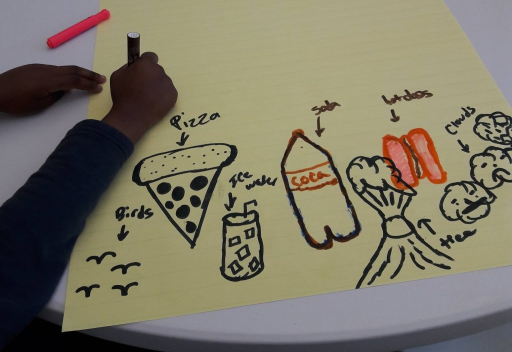 a young person's hand draws pictures on a large piece of paper